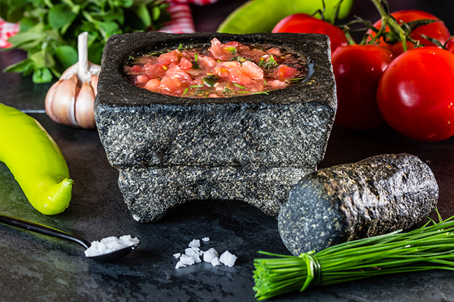 Tomato sauce salsa and ingredients dark stone background