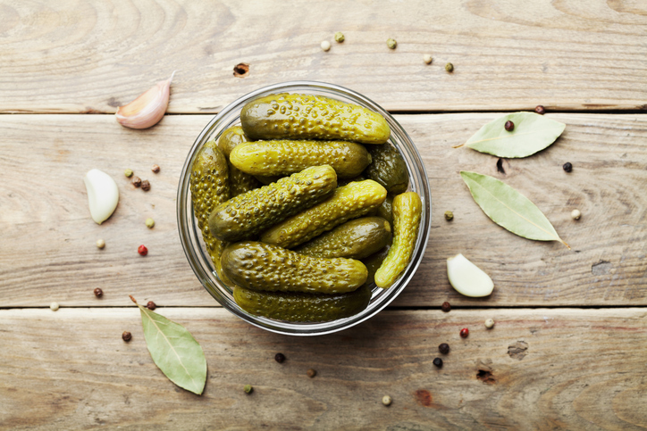 Pickled gherkins or cucumbers on wooden rustic table. Flat lay.