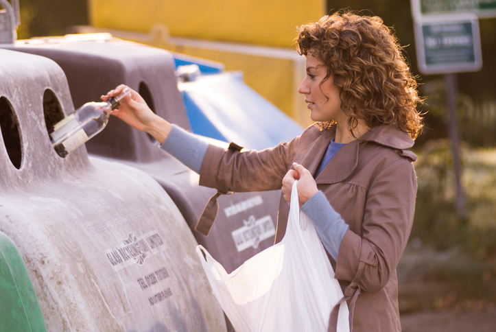 Young woman putting a bottle in a recycling bin