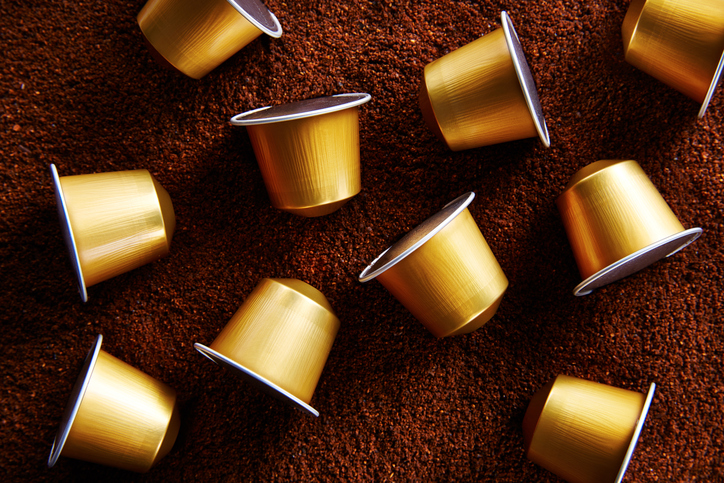 Gold capsules on coffee background