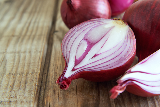 Red onion on wooden background