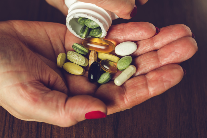 Woman's hands poured the mix of vitamins and nutritional, dietary supplement pills from a bottle, close-up.