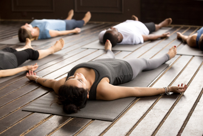 Group of sporty people in Savasana pose