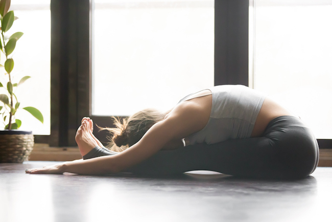 Young attractive woman in paschimottanasana pose, home interior