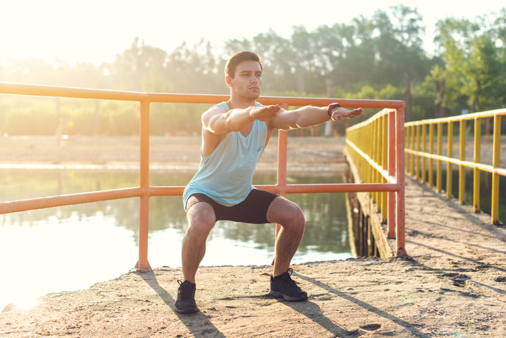 Fit man warming up doing squats stretching arms forward outdoors.