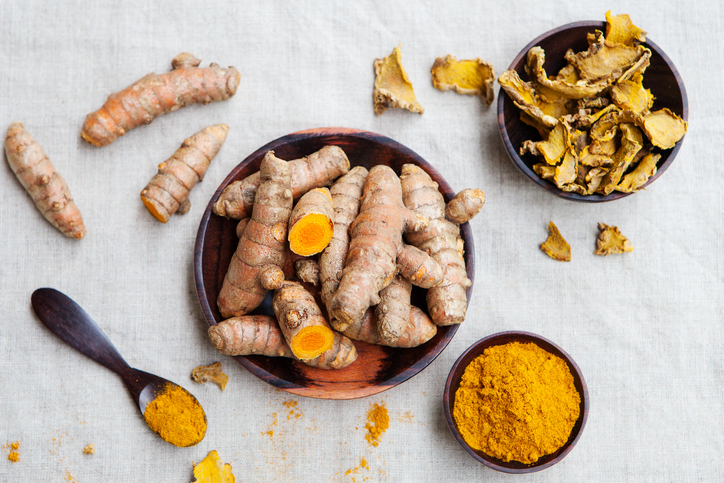 Fresh and dried turmeric roots in a wooden bowl
