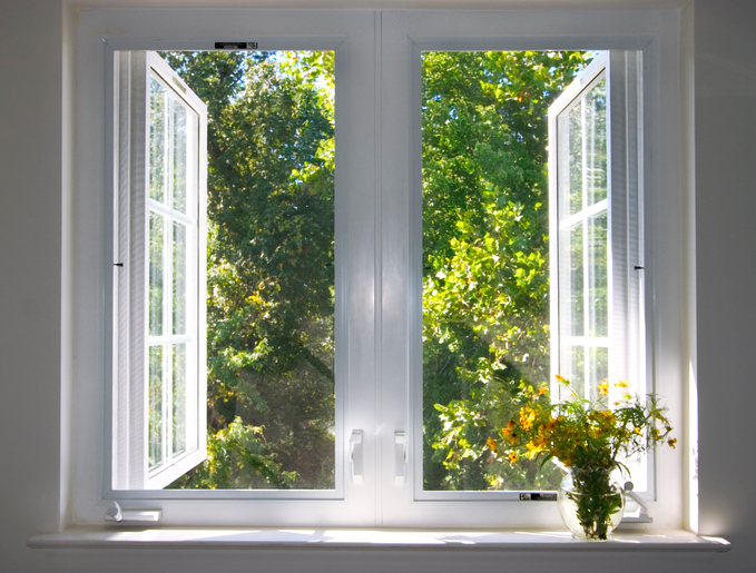 A window is open to a view of trees.