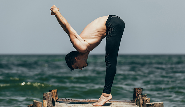 side view of shirtless man practicing yoga in uttanasana pose on pier
