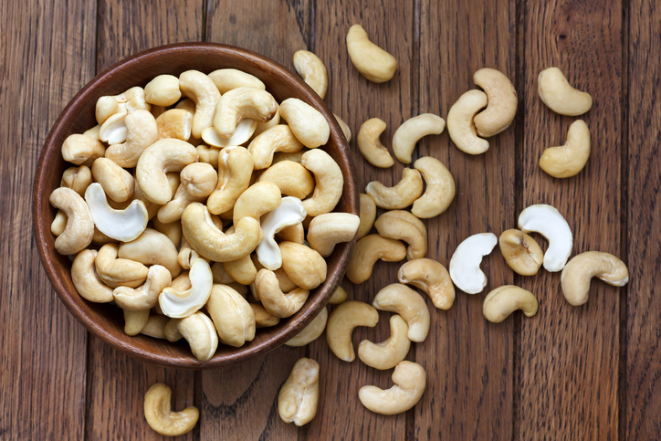 Wooden bowl of cashews with more cashews scattered around