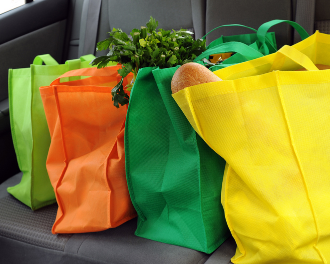 Four colorful eco-friendly reusable bags filled with groceries in the back seat of a car.