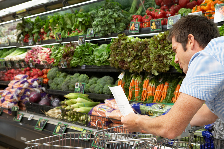 A man looks at his grocery list while in the produce aisle.