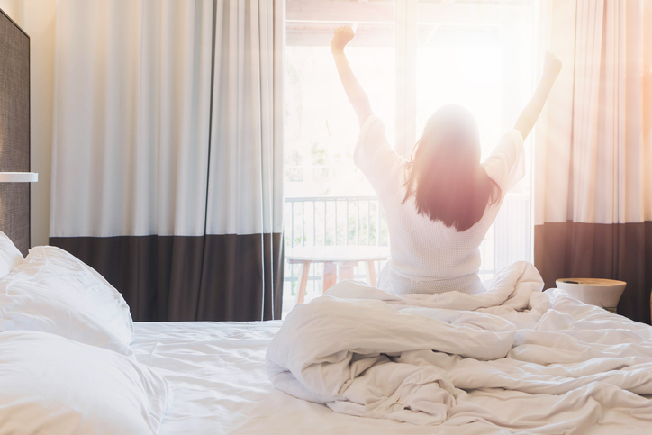 A woman stretches in bed as sun comes through the window.