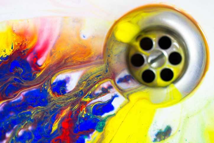 colorful paint goes down a drain