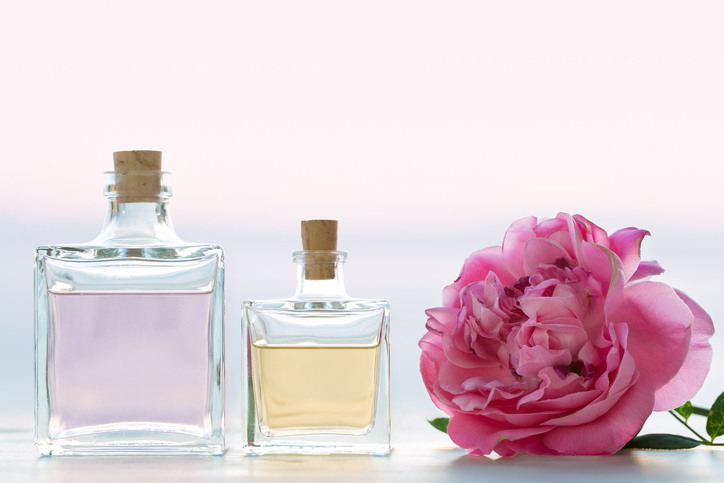 two bottles of perfume next to a flower