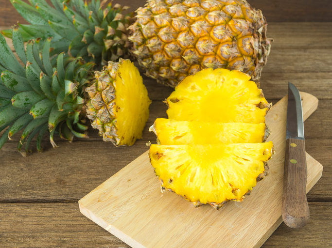 pineapple and pineapple slices on wooden table