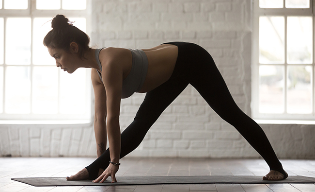 Young attractive woman in Ardha Parsvottanasana pose, white loft