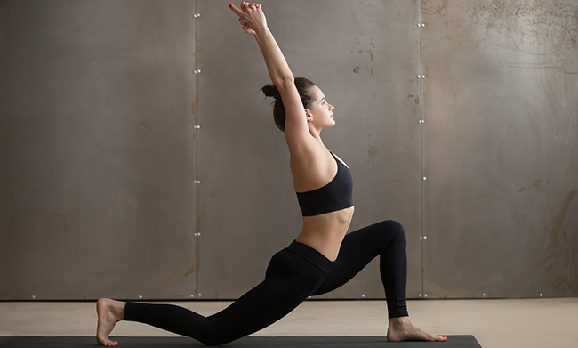 Young attractive woman standing in anjaneyasana pose, grey studi
