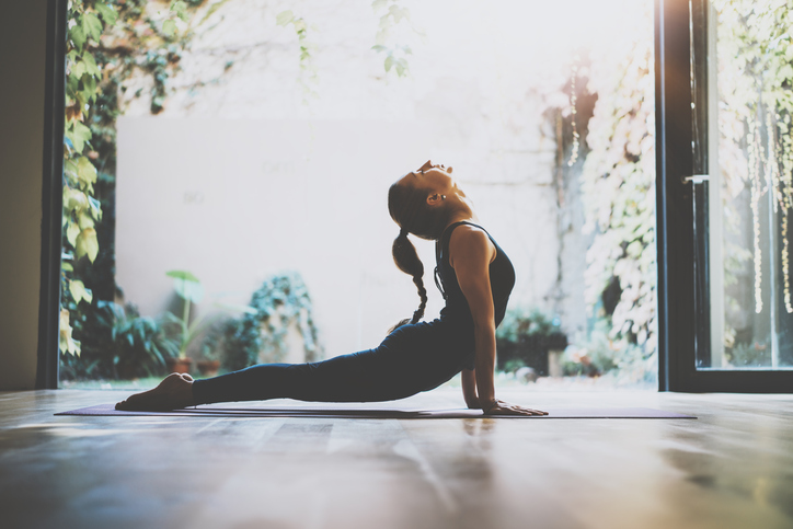 Portrait of gorgeous young woman practicing yoga indoor. Beautiful girl practice cobra asana in class.Calmness and relax, female happiness.Horizontal, blurred background.Visual effects.