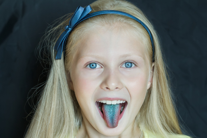portrait of teenage blonde girl sticking out her tongue dyed blue