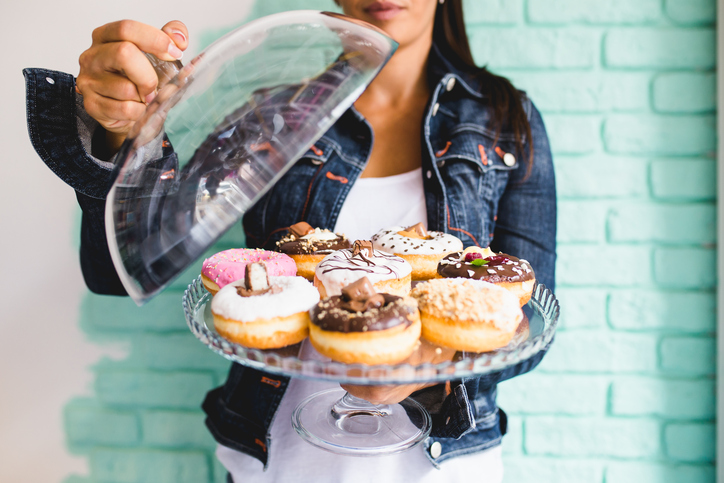 a woman holds a plate of doughnuts