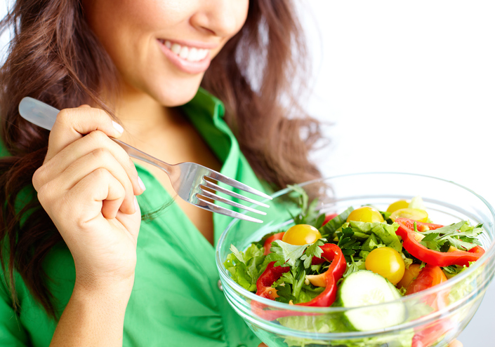 A woman eats a salad.
