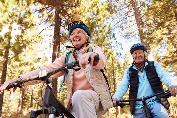 Senior couple mountain biking on a forest trail