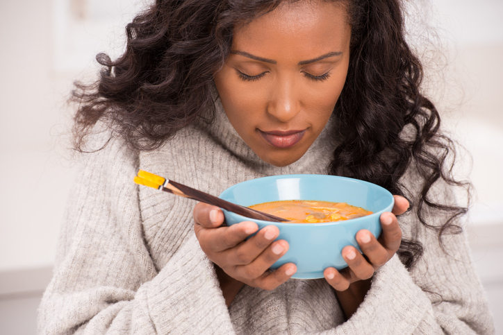 a woman holds up her bowl of soup to smell it