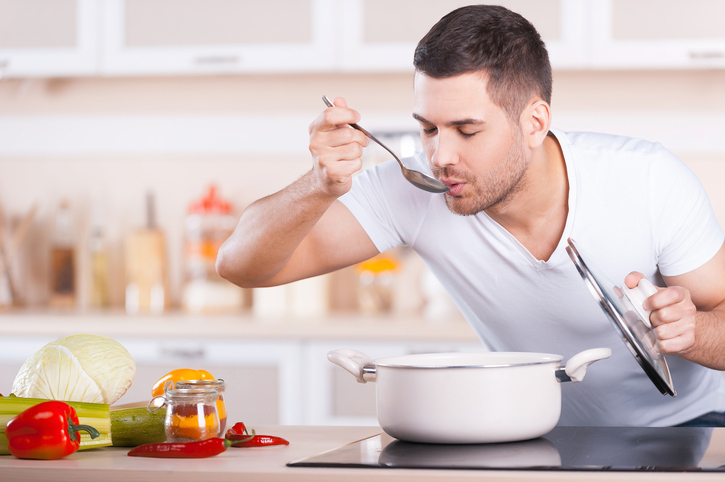 man tasting soup from the pot while standing in the kitchen