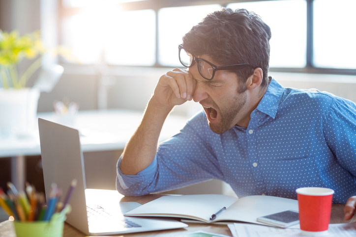 Male businessman yawning in office