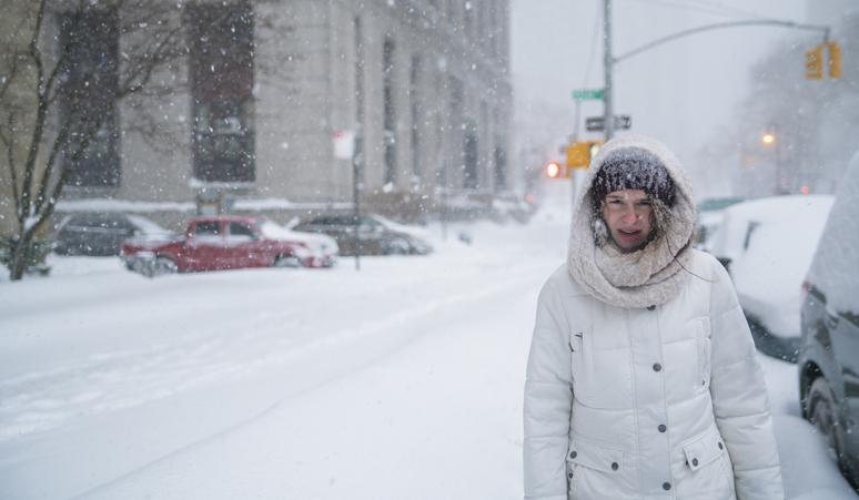 Teenager girl walks under snowfall at the street in Manhattan