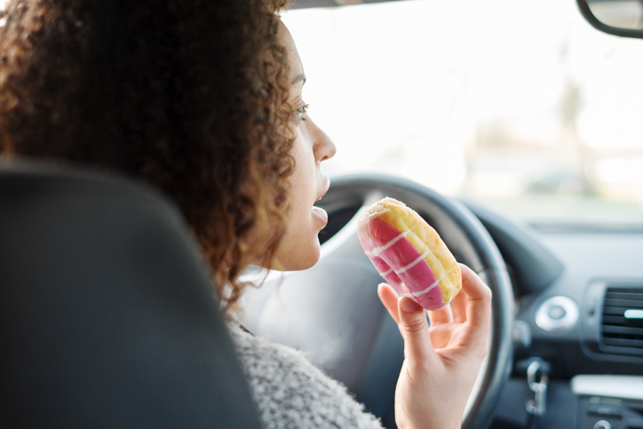 Woman eating a sweet driving a car