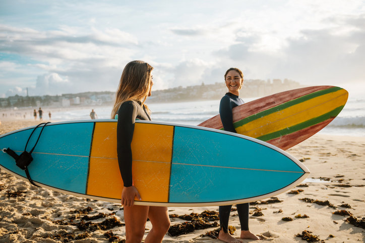 Two female friends with surfboards
