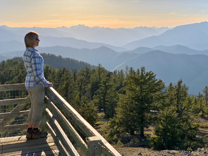 Ordinary middle age woman hiker on the balcony of fire watch tower enjoying beautiful views of mountains at sunset.