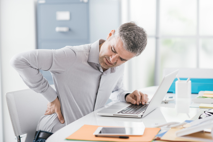 man sitting at desk experiencing back pain