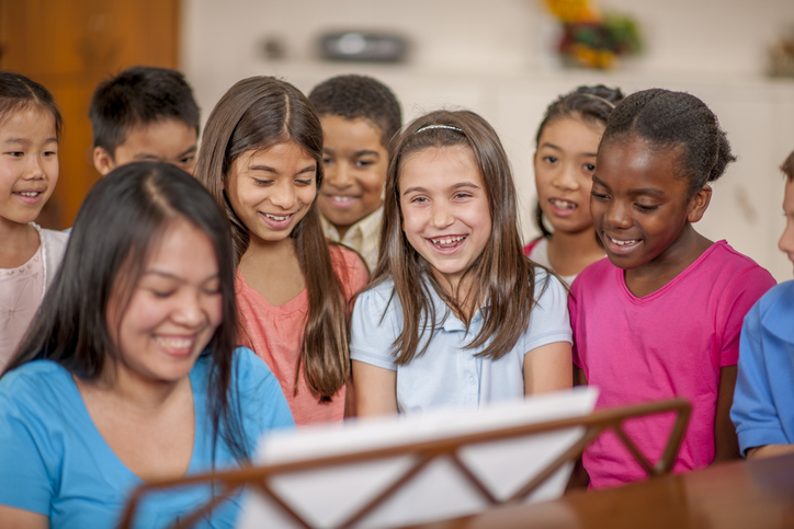 A group of children sing while one plays piano.