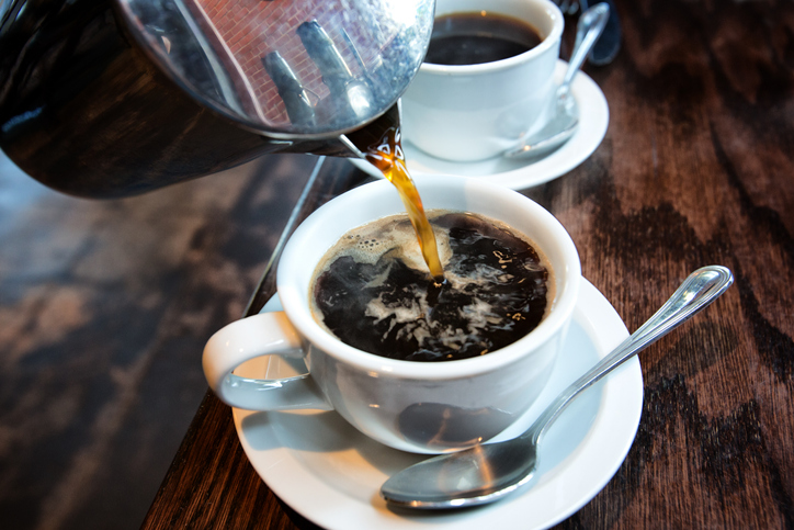 Fresh hot coffee being poured into a cup from a stainless steel french press