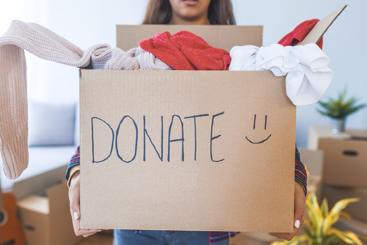 woman carrying a donation box of clothes
