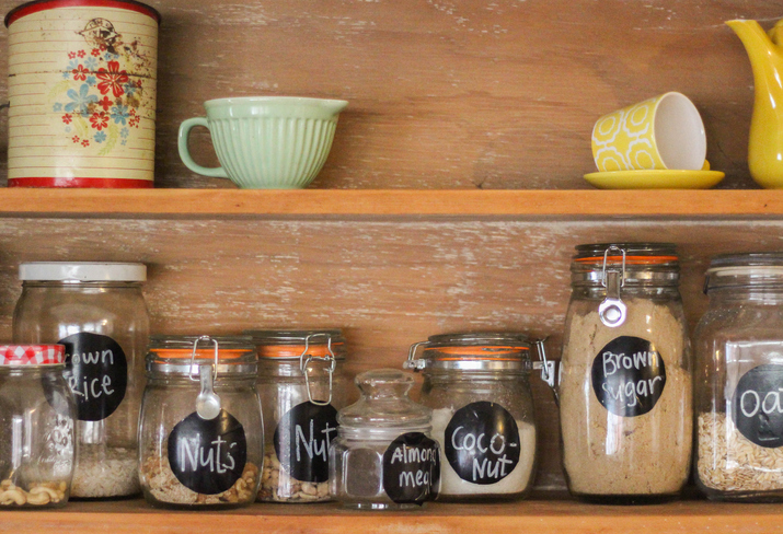 labeled jars of food on a kitchen shelf