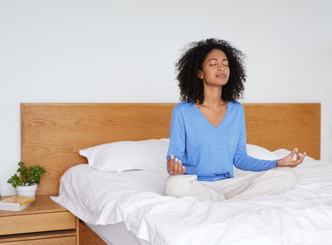 a woman sits in her bed meditating