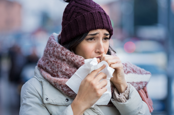 Woman coughing with a tissue outside in winter