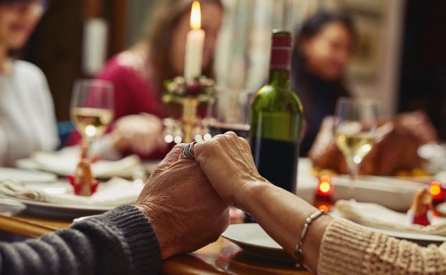 mother and father holding hands at thanksgiving table