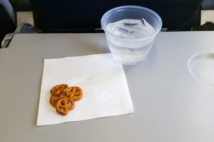 airplane tray table with water and pretzels