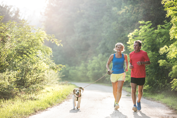 a couple jogs outside with their dog