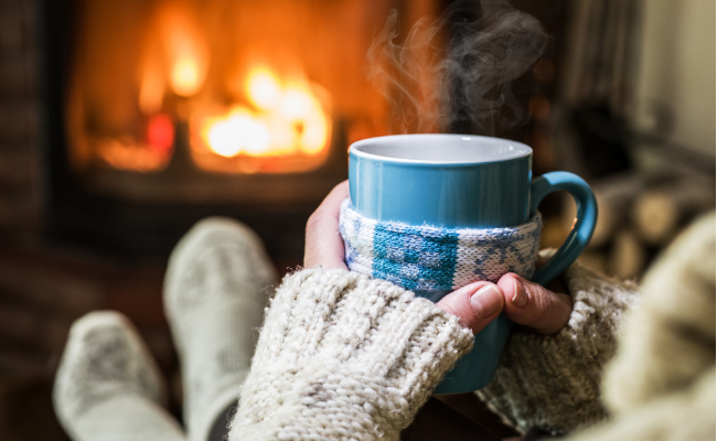 woman holding hot drink by fireplace