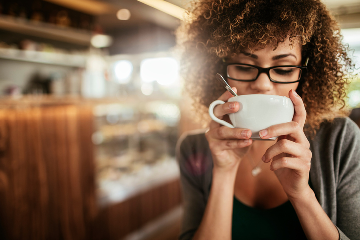 A woman drinks a cup of coffee in a coffee shop.