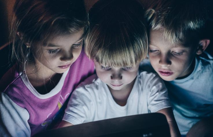 Three kids looking down at monitor
