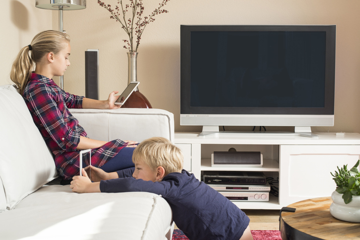 Children using tablet and smartphone in living room