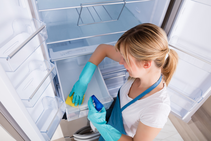 woman cleaning an empty refrigerator drawer
