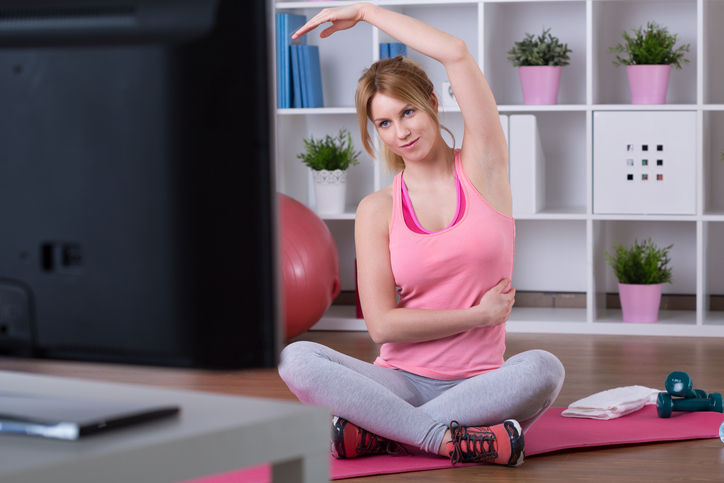 A woman exercises in front of the TV.