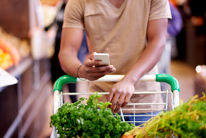 A person checks their grocery list on their phone while grocery shopping.